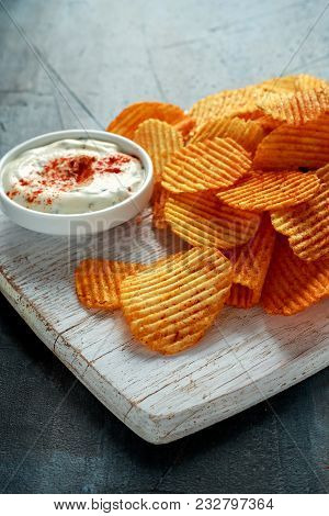 Potato Chips, Snack Crisps With Red Paprika And White Dip Sauce On White Board