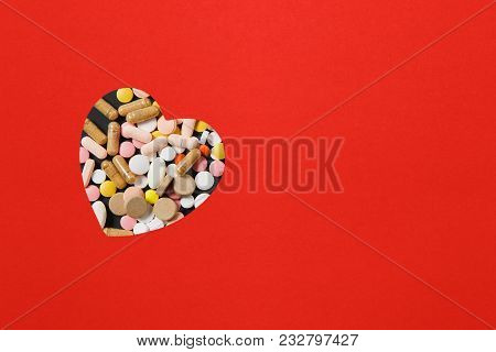 Medication White Colorful Round Tablets Arranged Abstract In Heart Shape On Red Color Background. Pi