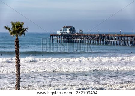 California Oceanside Pier Over The Ocean With Paln Trees And Beach, Travel Destination