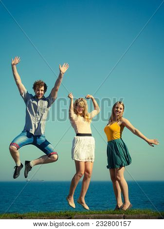Carefree Young Friends People Jumping By Sea Ocean Water. Happy Women And Man Having Fun. Summer Hap