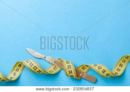 Plastic surgery of the body and face. Surgery for weight loss, liposuction, skin tightening, remove fat. Scalpel and yellow measuring tape. Copy space for text poster