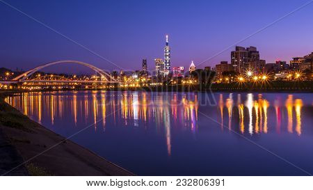 Night Light Cityscape Of Taipei City Beside The River And Bridge With Reflection At Twilight Time