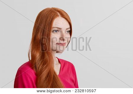 Sideways Portrait Of Thoughtful Freckled Ginger Female Model Remembers Some Pleasant Moments In Life