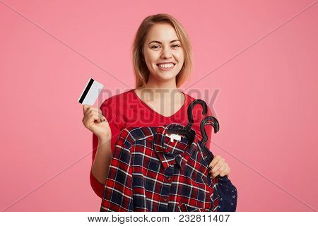 Glad Positive Female Holds Clothes On Hangers And Plastic Card, Going To Pay For New Purchase, Enjoy