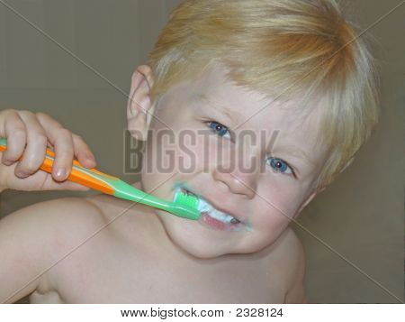 a young boy is brushing his teeth poster