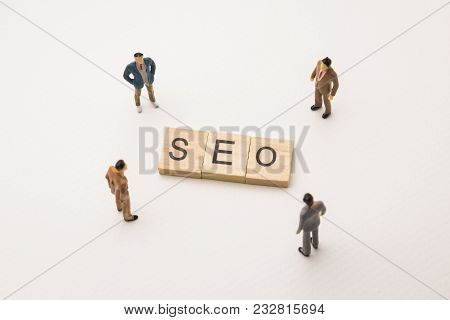 Miniature Figures Businessman : Meeting On Seo Letters By Wooden Block Word On White Paper Backgroun