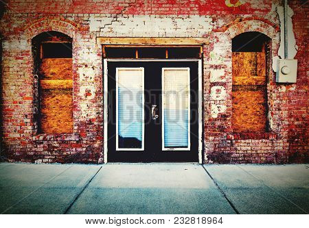 A Sidewalk View Of A Colorful Antique Brick Storefront With Double Doors And Arched Windowsill In A