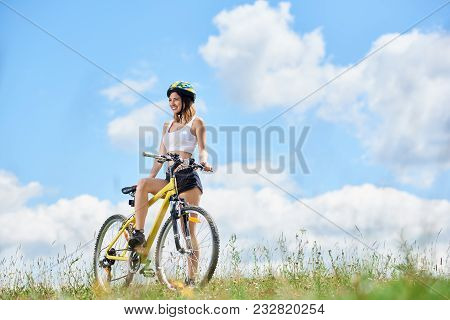 Happy Young Female Rider Cycling On Yellow Bicycle On A Grass, Wearing Helmet, Enjoying Sunny Day In