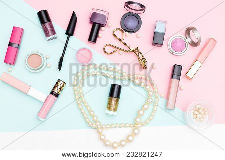 Decorative Cosmetics And Pearls On A Pink Background. Flat Lay