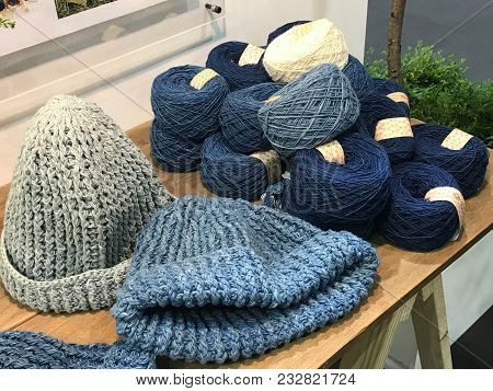 Natural Color Of Indigo Blue Hand Made Crochet Hat With Pile Of Thread Or Yarn In Clothes Shop