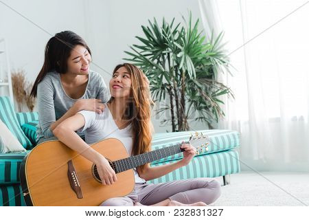 Asian Young Lesbian Couple Playing Guitar For Her Lover With Love Moment In The Bedroom Surrounded W
