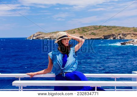 Happy Redhead Girl In Blue Dress And Hat Have A Voyage On A Boat In Greece. Summertime Vacation Conc