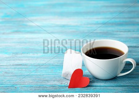 Cup Of Coffee With Red Heart And Teabag On Wooden Table