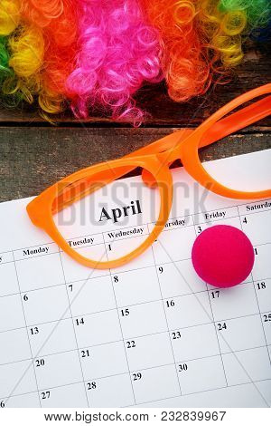April Calendar With Glasses And Wig On Wooden Table