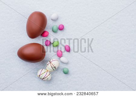 Chocolate Easter Eggs, Sweets And Copy Space. Styrofoam Easter Eggs, Chocolate Eggs And Candies On L