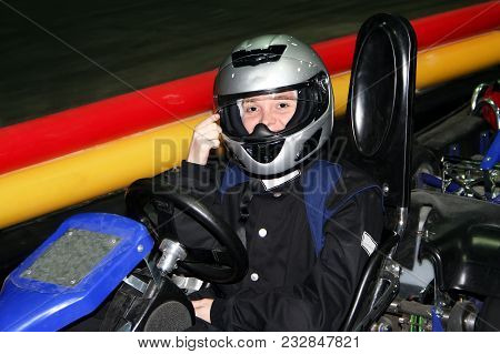 A Smiling Girl In Kartings Clothes Is In A Go-kart Indoors