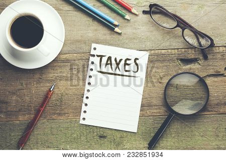 Taxes Text On Notebook With Coffee And Stationery