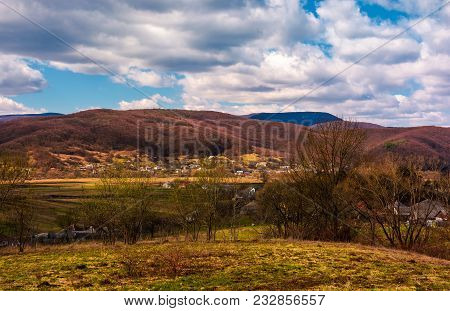 Mountainous Countryside In Springtime. Lovely Rural Scenery Near The Village On A Cloudy Day