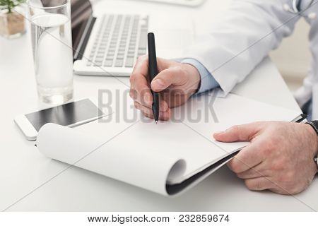 Unrecognizable Male Doctor Writing Notes In Clipboard While Working At Her Office. Always Ready To H