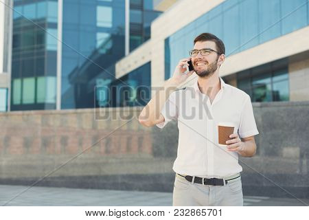 Handsome Happy Businessman Is Talking On Cell Phone And Drinking Coffee While Standing In Front Of M