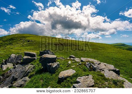 Huge Cloud Rising Behind The Hill. Gorgeous Mountain Landscape With Boulders On Grassy Slopes