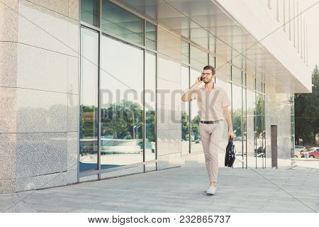 Confident Young Businessman Talking On Cell Phone And Carrying Briefcase While Walking Near Modern O