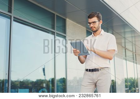 Attractive Concentrated Businessman Or Lawyer In Eyeglasses Is Touching His Digital Tablet Screen Wh