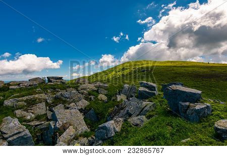 Giant Boulder On The Grassy Hillside. Beautiful Summer Landscape In Mountains. Fine Weather With Som