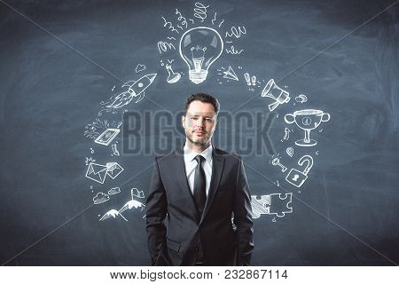 Presentation And Plan Concept. Portrait Of Handsome European Businessman Standing On Chalkboard Wall