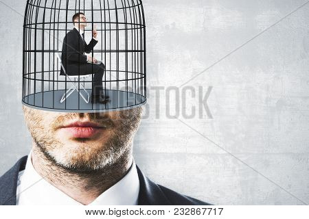 Cage Headed Businessman On Concrete Wall Backdrop With Copyspace. Freedom And Innovation Concept
