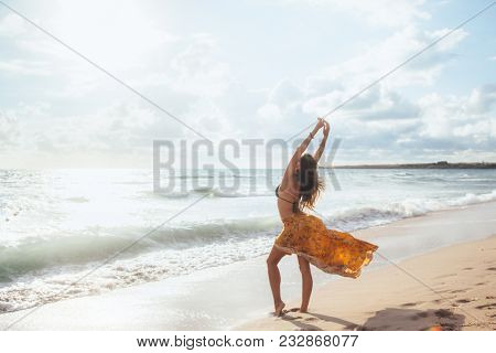 Girl wearing floral maxi skirt walking barefoot on the sea shore. Bohemian clothing style.