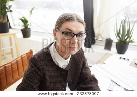 Close Up Portrait Of Attractive 60 Year Old Caucasian Woman Designer With Gray Hair Wearing Rectangu