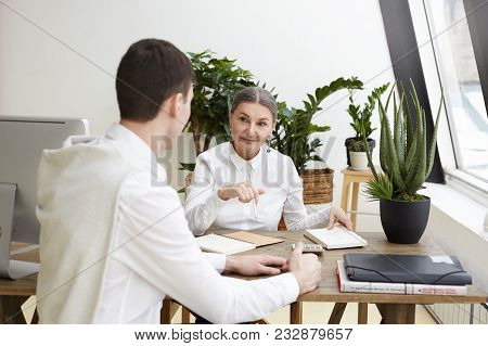 Candid Shot Attractive Confident Middle Aged Female Employer Sitting At Desk With Copybook, Making N