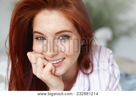 Picture Of Charming Young Female With Loose Red Hair And Freckles Lying On Bed At Home, Keeping Hand