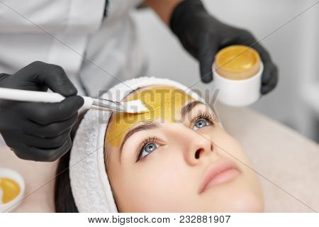 Close Up Of Beautician Applying Gold Mask On Face Of Gorgeous Woman In Beauty Salon. Beautiful Clien