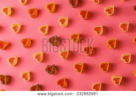 Minimalism style. Repetition concept. View from above on pasta pattern with heart shape, on colored background. poster