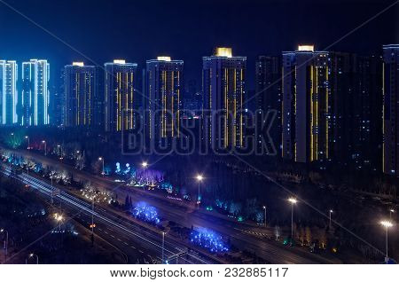 Looking On The Illuminated Skyscrapers In A Row And A Motorway By Night, Shenyang, China