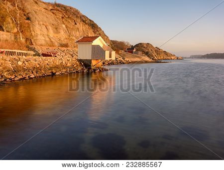 A Bathing Cabin On West Coast Of Gothenburg During Golden Hour Of Sunset. Beautiful Golden Light Of