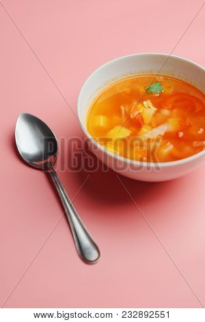 Hot Vegetable Soup With Chicken Meat In A Bowl. A Leaf Of Greenery. On A Pink Background. The Concep
