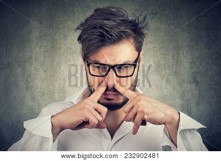 Man Pinches Nose With Fingers Looks With Disgust Something Stinks Bad Smell Isolated On Gray Backgro