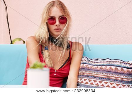 Blonde Female With Serious Look Wears Red Sunglasses, Tank Top, And Bandana On Neck, Poses In Cozy R