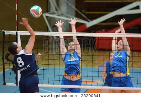 KAPOSVAR, HUNGARY - APRIL 24: Marianna Palfy (C) blocks the ball at the Hungarian NB I. League woman volleyball game Kaposvar (blue) vs Ujbuda (black), April 24, 2011 in Kaposvar, Hungary.