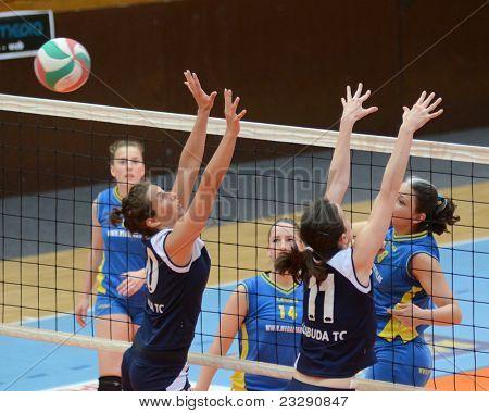 KAPOSVAR, HUNGARY - APRIL 24: Barbara Balajcza (R) strikes the ball at the Hungarian NB I. League woman volleyball game Kaposvar (blue) vs Ujbuda (black), April 24, 2011 in Kaposvar, Hungary.