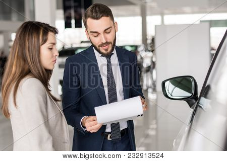 Waist Up Portrait Of Handsome Car Salesman Talking To Young Woman Helping Her Choose  In Car Showroo