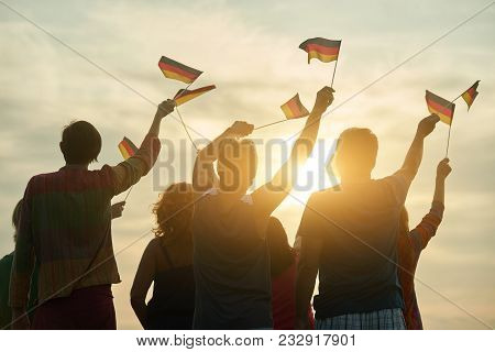 Crowd Of People Holding Deutsch Flag, Back View. Silhouette Of Patriotic German Family, Rear View.