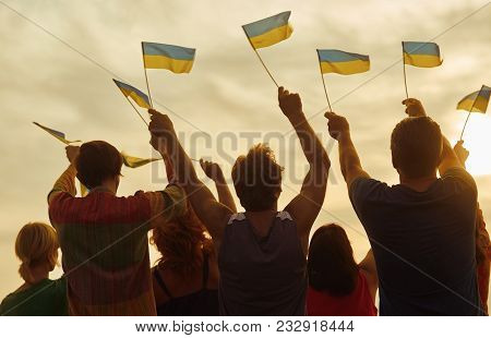 Ukrainian Patriots With Small Flags. Ukraine Family Against Evening Sky Background.