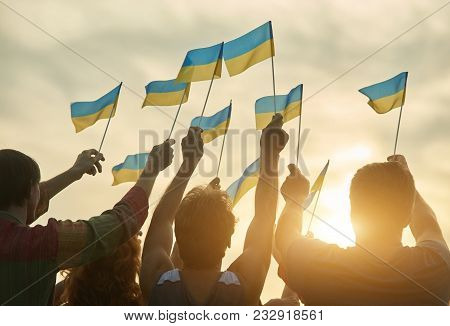 Crowd With Ukrainian Flags In The Evening. Ukrainian Revolution. Evening Sunny Sky Background.
