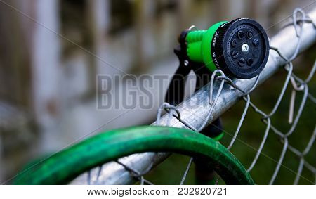 Green Garden Hose Nozzle On A Fence Near An Over Hanging Hose