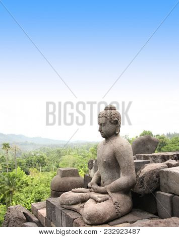 Ancient statue of a meditating Buddha in Borobudur Buddhist Temple, Java Island, Indonesia. On blue sky background