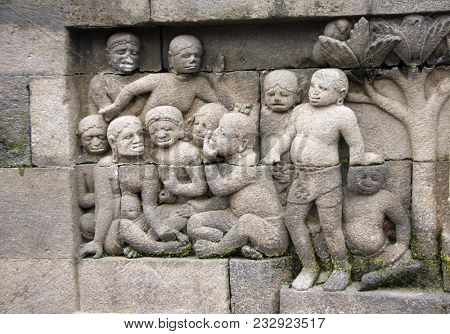 Ancient stone bas-relief with group of people - mens and womens, Buddist temple Borobudur, Yogyakarta, Central Java, Indonesia. UNESCO world heritage site